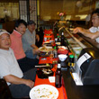 People enjoying sushi at the bar.